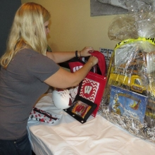 Caitlin Waldhart prepares a UW Tailgate Experience auction package for display.