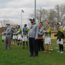 Owern and coach Tim Debyl (center) looks-on along with Assistant Coach Jacob Spiro (left) and the Radicals bench.