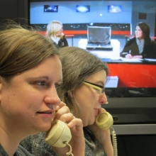 Phone workers in Hour 3 field answers while UTVS hosts television coverage in the background.