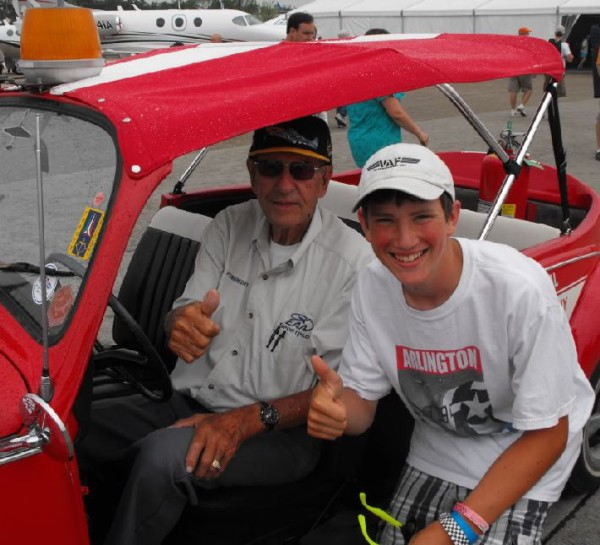 "Paul Poberezny's trademarek was the ""thumbs up"" and countless photos of him with admirers. A fixture at the convention was Paul in his convertible VW Bug ""Red One"". Areas of the Oshkosh fly-in were color designated and had corresponding VW bugs. Courtesy: Vansairforce.com"