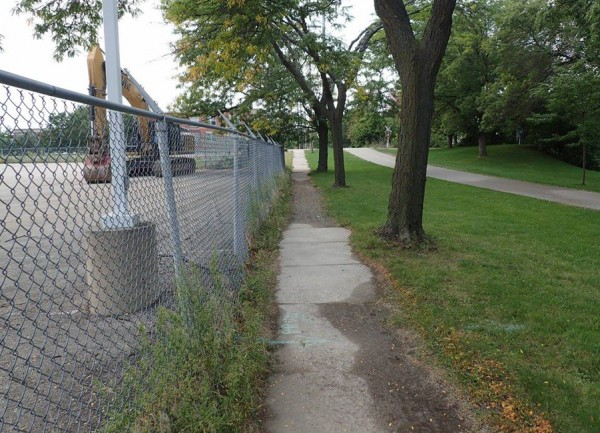 The light blue spray painted line on the path marks a sewer line that runs from the site to a open grate in the grass to the right. Residents are very concerned about contaminated site runoff with Yahara river so close by. Courtesy: FB/DOA Demolition